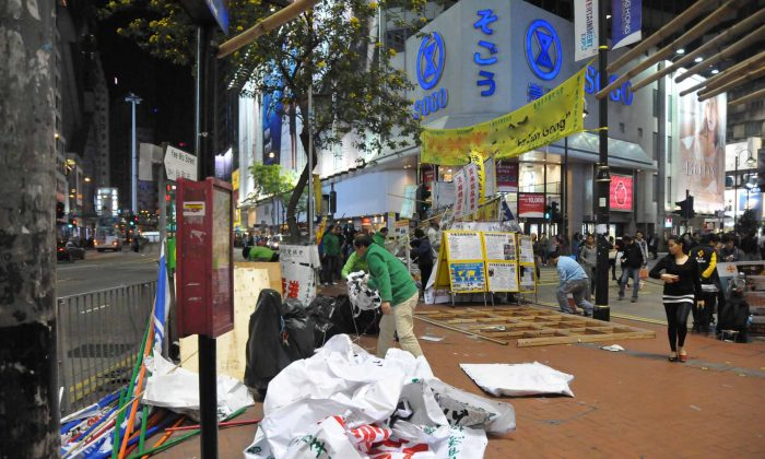 Hong Kong Youth Care Association members take down the banners they had used to obscure the Falun Gong information site outside the popular Sogo department store in Causeway Bay, Hong Kong. The removal of the Youth Care Association banners marks the end of almost 10 months harassment of Falun Gong practitioners by the Chinese Communist Party front group. (Bill Cox/The Epoch Times)