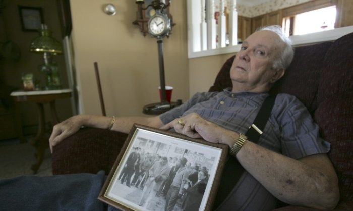 """In this Wed., March 4, 2009, file photo, Elwin Hope Wilson holds a framed photo he kept showing a mob he participated in during one of local civil rights """"sit-ins"""" that took place in the early 1960s, in Rock Hill, S.C. The South Carolina man who publicly apologized for years of violent racism, including the beating of a black Freedom Rider who went on to become a Georgia congressman, died Sunday, March 31, 2013. He was 76. (Mary Ann Chastain/AP)"""