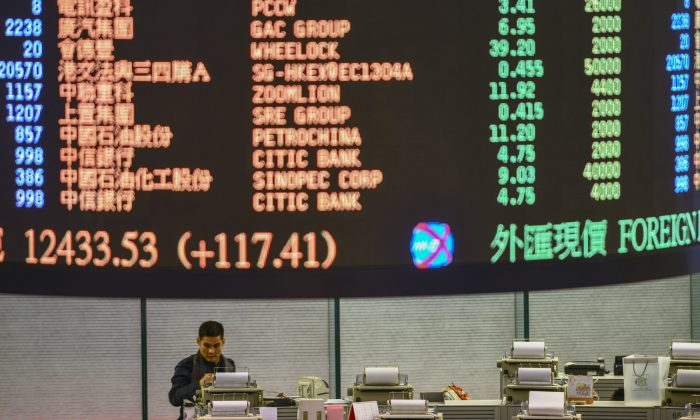 A trader walks the floor of the Hong Kong Stock Exchange as share prices are flashed above on Jan. 2, 2013. Economists are concerned of the consequences of the massive debt accumulated in China. (Antony Dickson/AFP/Getty Images)