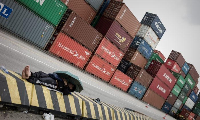 A docker rests in front of containers at the Kwai Chung container terminal in Hong Kong on March 29, 2013. Chinese officials have recently been accused of cooking the books on import and export numbers related to Hong Kong. (Philippe Lopez/AFP/Getty Images)