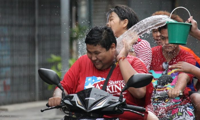 A motorcyclist and his passenger get a bucket full of water during this year's roadside celebrations for Songkran (Thai New Year). Held during April 13-16, Songkran is Thailand's biggest family orientated period of the year. (James Burke/The Epoch Times)