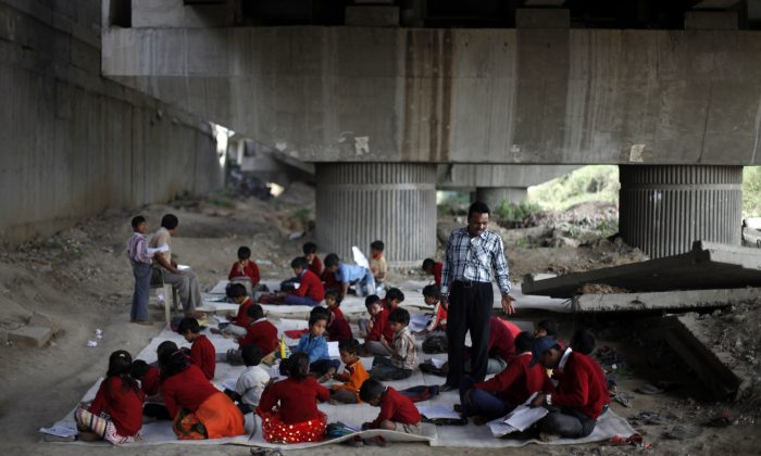 """Rajesh Kumar, the founder of a free school for slum children, teaches a class at a free school for impoverished children under a mass transit bridge in New Delhi, India on March 13, 2013. Kumar fears his project is precarious. He needs more volunteer teachers because of the mass of students, but doesn't know where to find them. And his unregistered school is squatting on railroad property. """"Whenever I am asked to leave this place, I will have to,"""" he said. """"Right now, the children are studying. We will take each day as it comes. As long as it remains possible, let's take advantage of it."""" (AP Photo/Altaf Qadri)"""
