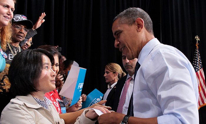 Karen Gao, from the Washington D.C. Falun Dafa Association, shakes hands with President Obama, and gives him a letter at a public campaign event at George Mason University in Fairfax, Va., on Oct. 5. The letter updates the president about the live, forced organ harvesting from Falun Gong practitioners by the Chinese Communist regime, and asks him to help end this atrocity. (The Epoch Times)