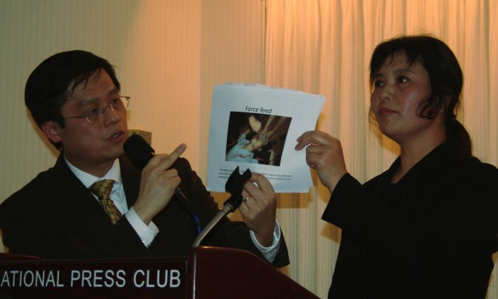 Falun Gong practitioner Chunmei Ma (R) holds up an illustration of the forced feeding torture that guards used on her in a forced labor camp. Her translator Frank Lee (L) is explaining the photo in English. Ma spoke April 24 about her experiences in a China forced labor camp. (Gary Feuerberg/ The Epoch Times)