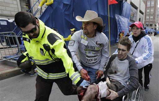 Carlos Arredondo is photographed helping Jeff Bauman past the finish line the 2013 Boston Marathon following an explosion in Boston, Monday, April 15, 2013.  (AP Photo/Charles Krupa)