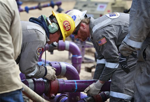 Workers adjust piping during a short pause in water pumping during a natural gas hydraulic fracturing operation at an Encana Oil & Gas (USA) Inc. drilling site outside Rifle, in western Colorado. (AP Photo/Brennan Linsley)