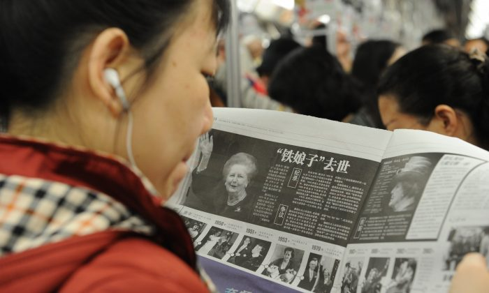 A Chinese woman reads about former British prime minister Margaret Thatcher's death the previous day on April 9, 2013. The Communist Party has now banned use of foreign reports by mainland media. (Peter Parks/AFP/Getty Images)