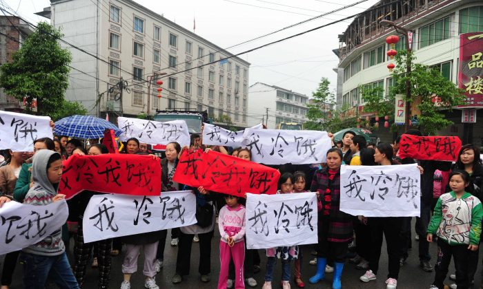 After an earthquake struck southwest China's Sichuan Province, residents in Lingguan township of Baoxing county gather on the street with banners saying 'I am cold and hungry' to appeal for support and to draw attention the shortage of relief supplies, on April 23, 2013. The Communist Party has been preventing volunteers from assisting victims in case the true number of casualties and the poor construction of the buildings is revealed. (AFP/Getty Images)
