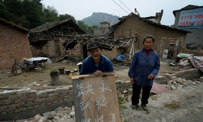 An elderly man holds a sign asking for help outside his destroyed home in Longmen village on April 22, 2013, after a magnitude 7.0 quake hit Sichuan Province on April 20. Two days after the quake, many villagers had not seen               official rescue teams, saying they have no water, food, or tents. (Mark Ralston/AFP/Getty Images)
