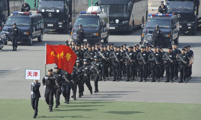 A team of Chinese special tactical police march during a demonstration in Beijing on April 12, 2011. According to a Defense White Paper, the Chinese regime deployed military police officers to handle domestic distrubances more than 1.6 million times in 2012, which He Qinglian says is a sign the regime and the people have become enemies