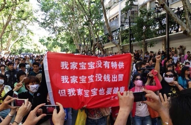 """Protesters hold up a banner about pollution, comparing their situation with that of communist officials. """"My child doesn't have a special supply of clean air, water or food, my child doesn't have money to go abroad, but my child needs to be healthy too!"""" (Weibo.com) This is what saying on the red banner."""