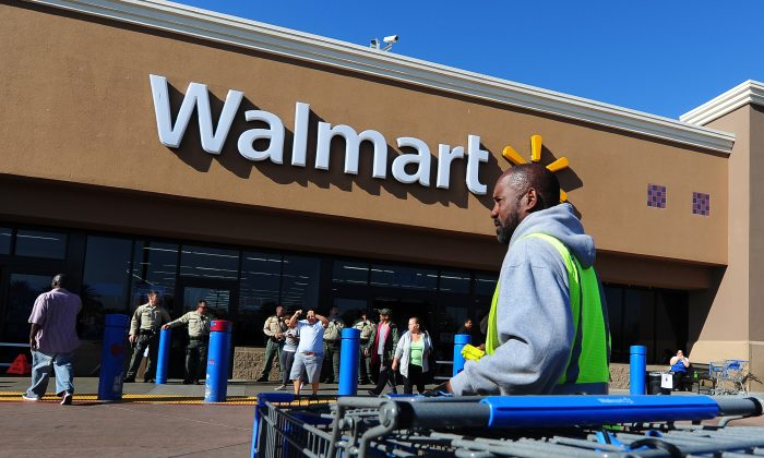 A Walmart employee gathers shopping carts in front of a Walmart store in Paramount, Calif., in 2012 in this file photo. Wal-Mart, the largest U.S. retailer, has been experiencing a slump in sales. (Frederic J. Brown/AFP/Getty Images)