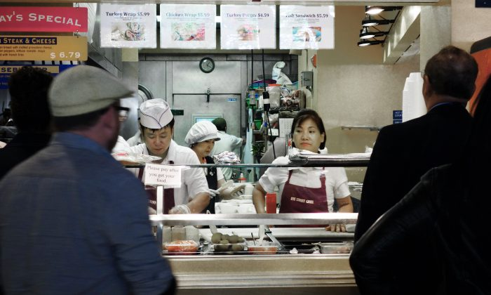 Customers wait to be served at a local neighborhood delicatessen on April 24, 2013 in downtown Washington. Americans have less disposable income while food prices are on the rise. (Paul J. Richards/AFP/Getty Images)
