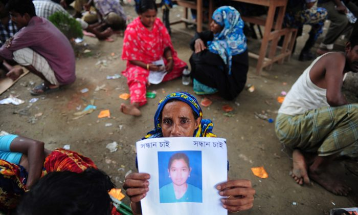 A Bangladeshi family member holds up the portrait of her missing relative, believed to be trapped in the rubble of an eight-story building collapse on the outskirts of Dhaka, on April 29, 2013. After hundreds died, the question arises whether global supply chains are at fault for the building's collapse. (Munir Uz Zaman/AFP/Getty Images)