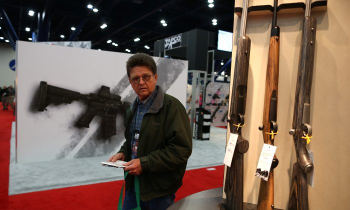 An attendee looks at a display of shotguns during the 2013 NRA Annual Meeting on May 3. A group wants to give out shotguns to people in 15 cities, and is beginning in Houston. (Justin Sullivan/Getty Images)