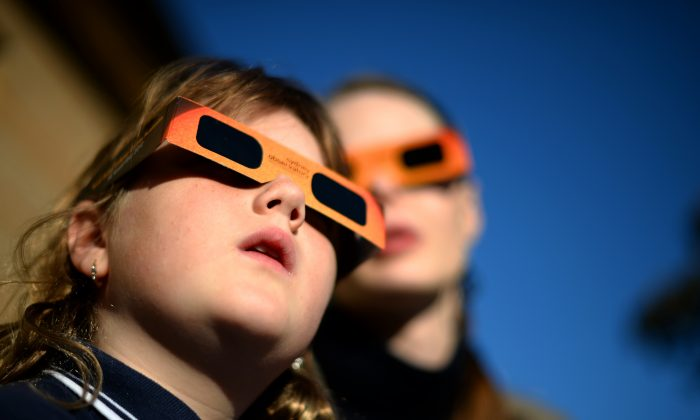 A child (L) watches a partial solar eclipse with a woman at the Sydney Observatory on May 10, 2013. Star-gazers were treated to an annular solar eclipse in remote areas of Australia with the Moon crossing in front of the Sun and blotting out much of its light. The annular eclipse, a phenomenal which occurs when the Moon is so close to the Earth that is cannot completely cover the Sun when it passes between it, was seen across a band across northern Australia, while places such as Sydney saw a partial eclipse. (SAEED KHAN/AFP/Getty Images)