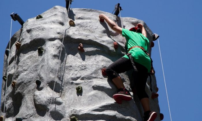 A student involved with a summer program for the Police Athletic League, climbs a rock climbing wall on July 10 in Manhattan. (Benjamin Chasteen/The Epoch Times)