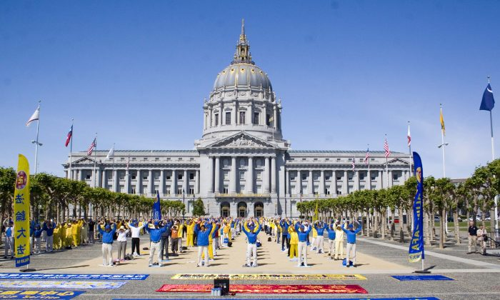 Falun Gong practitioners perform exercises in front of City Hall in celebration of World Falun Dafa Day in San Francisco, Calif., on May 11, 2013. The traditional Chinese spiritual practice was first introduced to the public 21 years ago and has spread to more than 100 countries. (Gary Wang/The Epoch Times)