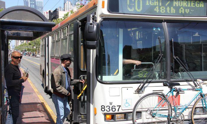 Passengers board a Muni bus on Market Street in San Francisco, Calif., May 28, 2013. (Christian Watjen/The Epoch Times)