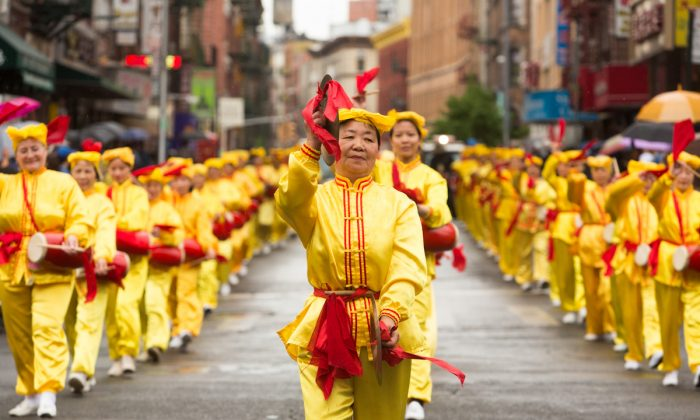 Falun Dafa practitioners perform on waist drums during a parade in Manhattan's Chinatown on May 18, 2013. (Matthias Kehrein/The Epoch Times)