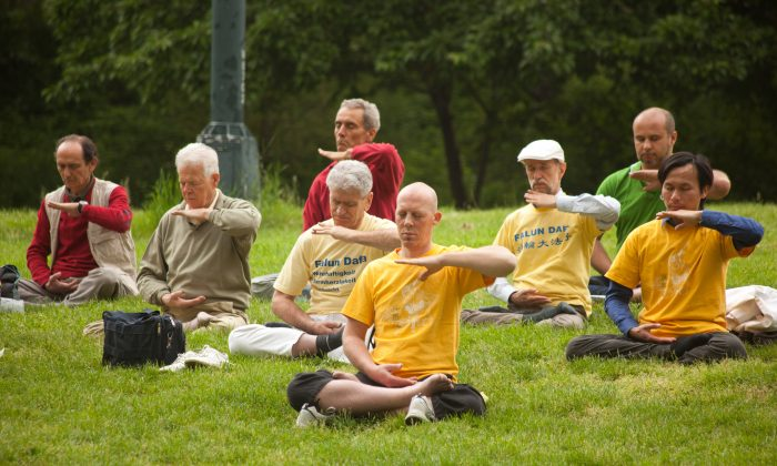 Adherents of Falun Dafa practice meditation in Central Park, New York on May 18. (Jeff Nenarella/The Epoch Times)