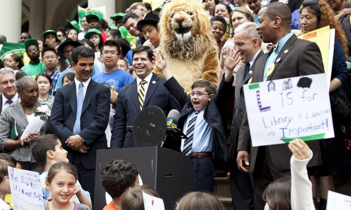 Third-grader Preston Ferraiuolo from Brooklyn speaks during a press conference on the City Hall steps to protest $106.7 million in budget cuts to public libraries. (Samira Bouaou/The Epoch Times)