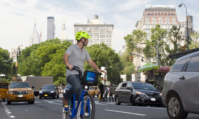 A man in a neon blue helmet rides a Citibike near Union Square on May 29. (Samira Bouaou/The Epoch Times)