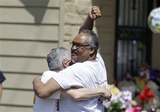 Felix DeJesus pumps his fist after bringing home his daughter, Gina, Wednesday, May 8, 2013, in Cleveland. DeJesus was one of  three women held captive for about a decade at a run-down Cleveland house. Ariel Castro, owner of the house, has been charged with rape and kidnapping. (AP Photo/Tony Dejak)