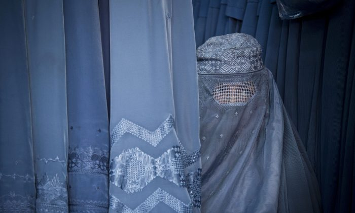 An Afghan woman peers through the  the eye slit of her burqa as she waits to try on a new burqa in shop in the old town of Kabul, Afghanistan. (AP Photo/Anja Niedringhaus, File)