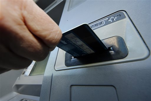A person inserts a debit card into an ATM machine in Pittsburgh in this file photo. (AP Photo/Gene J. Puskar, File)