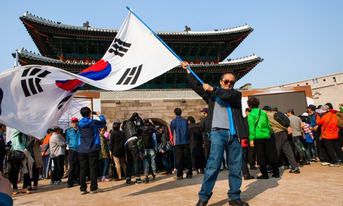 A man waves the South Korean flag in front of Namdaemun on the afternoon of its reopening on May 4, 2013. (Jarrod Hall/The Epoch Times)