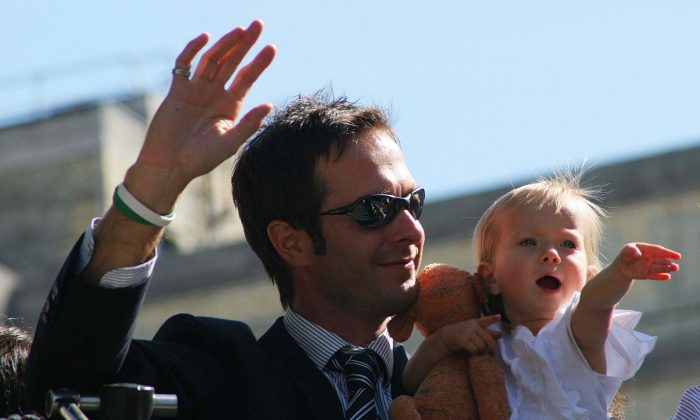 Captain Michael Vaughan and his daughter Talulah Grace wave to the crowd as the England Cricket team enter Trafalgar Square as part of the Ashes victory celebration on September 13, 2005. (Miles Willis/Getty Images)