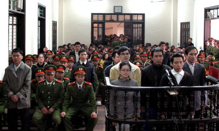 """A group of activists accused of plotting to overthrow the communist regime listen to verdicts at a court in the northern Vietnamese city of Vinh. One of the activists, blogger Dang Xuan Dieu, accused Vietnamese authorities of """"trampling on the eternal good morals of the Vietnamese nation."""" (Vietnam News Agency/AFP/Getty Images)"""
