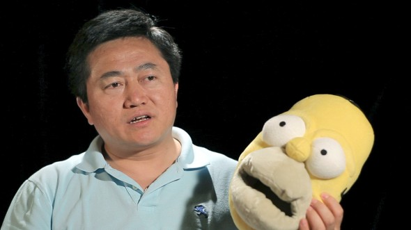 """In a scene from the documentary """"Free China: The Courage to Believe,"""" Charles Lee shows a pair of Homer Simpson slippers, which is similar to the product he made while incarcerated in a Chinese labor camp. (Courtesy of NTD Television)"""