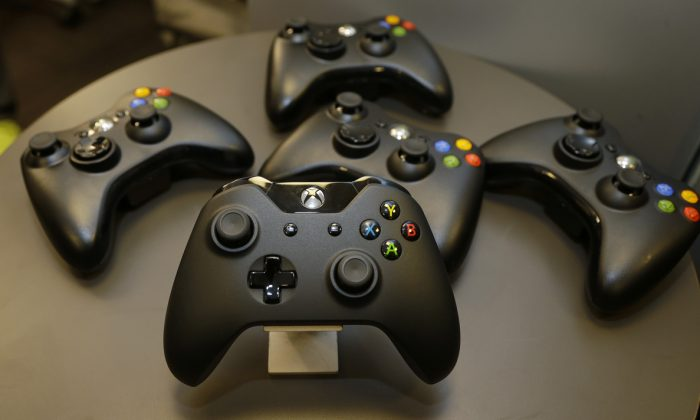 Controllers for Microsoft's Xbox One console is shown front and center with older-generation controllers behind it, in this file photo. (AP Photo/Ted S. Warren)