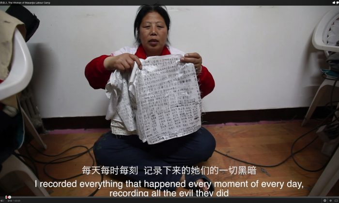 """Liu Hua holds up the diaries of torture and abuse that she had smuggled from the labor camp. After saying the line that appears in the subtitle in this picture, she said: """"And had the women smuggled it out their vaginas."""" (Screenshot via The Epoch Times)"""