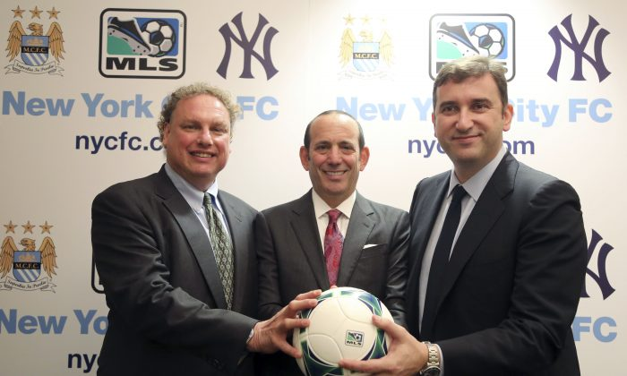 New York Yankees president Randy Levine, left, Major League Soccer Commissioner Don Garber, center, and Manchester City CEO Ferran Soriano pose for a photo at the MLS headquarter in New York, Tuesday, May 21, 2013. The New York Yankees are partnering with Manchester City to own Major League Soccer's 20th team, which will be called New York City Football Club and plans to start play in the 2015 season. (AP Photo/Mary Altaffer)