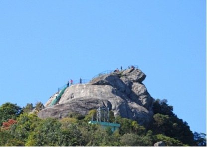 Tourists stand atop Eagle Beak Rock near Zhuming Cave. (Luofu Mountain Administration)