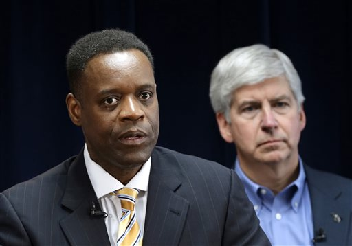In this March 14, 2013 file photo, Kevyn Orr, Detroit's state-appointed emergency manager, speaks at a news conference in Detroit as Michigan Gov. Rick Snyder listens. Mr. Orr finally announced a restructuring plan for the bankrupt city June 14. (AP Photo/Paul Sancya, File)
