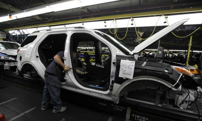 In this Dec. 1, 2010 file photo, plant employees assemble a 2011 Ford Explorer on the assembly line at Ford's Chicago Assembly Plant. (AP Photo/M. Spencer Green)