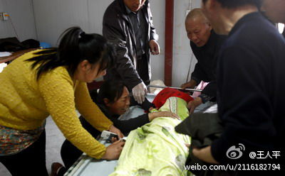 Distraught relatives at the bedside of one of two girls who died, after a principal from a rival kindergarten sought to poison some of the students at their school. (Weibo.com)