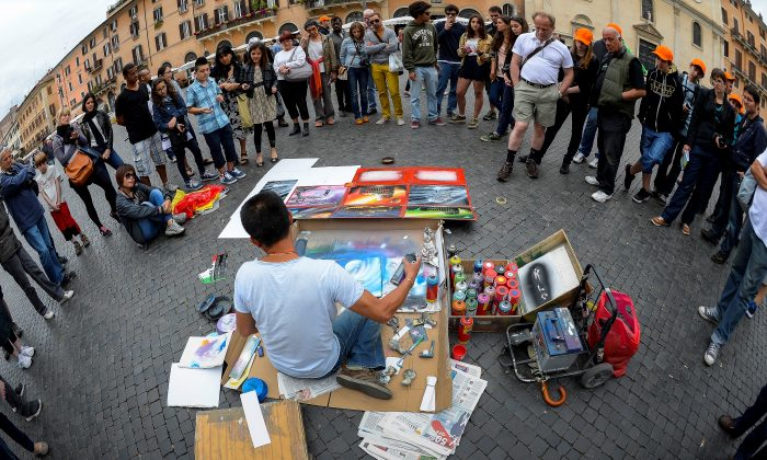 A street artist paints in front of people, at Piazza Navona in central Rome on May 21, 2013. (ANDREAS SOLARO/AFP/Getty Images)