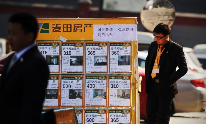 A real estate agent checks a property advertising board in Beijing on April 1, 2013. The rapidly inflating real estate market in major cities has slowed, following new cooling off policies by China's State Council. (Wang Zhao/AFP/Getty Images)