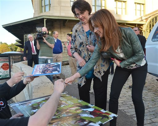 """The """"Office"""" actors, Phyllis Smith and Ellie Kemper, sign autographs outside the Radisson Lackawanna Station Hotel in Scranton, Pa., on May 3, 2013. (Scranton Times & Tribune, Jason Farmer/AP Photo)"""
