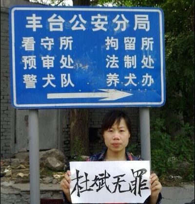 """Du Jirong, sister of human rights activist Du Bin, holds up a sign saying """"Du Bin is innocent."""" outside the Fengtai District Public Security Bureau. (China Human Rights Defenders)"""