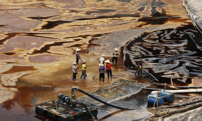 """Workers drain away polluted water near the Zijin copper mine in Shanghang on July 13, 2010, after pollution from the mine contaminated the Ting River, a major waterway in southeast China's Fujian Province. Such pollution has been an integral part of the development of China's economy—the """"China model"""" that the Chinese regime is now exporting around the world. (STR/AFP/Getty Images)"""