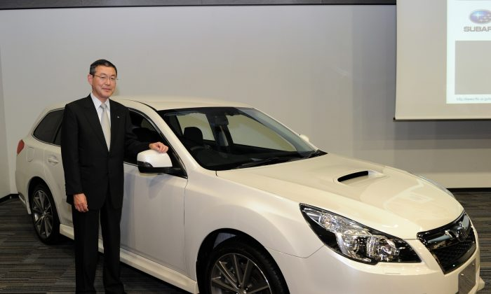 """Subaru President Yasuyuki Yoshinaga poses next to the SUV """"Legacy"""" in Tokyo on May 8, 2012. (YOSHIKAZU TSUNO/AFP/GettyImages)"""
