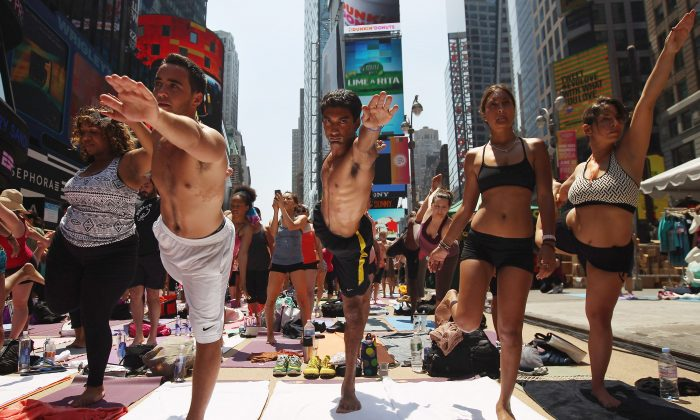 NEW YORK, NY-People brave high temperatures while practicing bikram yoga as part of the annual Mind Over Madness event in Times Square on June 20, 2012 in New York City. (John Moore/Getty Images)