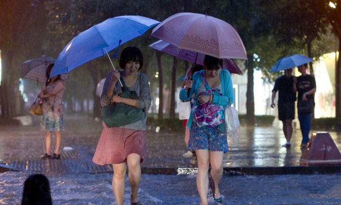 Two women cross a flooded street during heavy rainfall in Beijing on July 21, 2012. Beijing is installing nets in up to 1,000 manholes to prevent people from falling in when covers are removed, by either thieves or floodwaters. (Ed Jones/AFP/Getty Images)