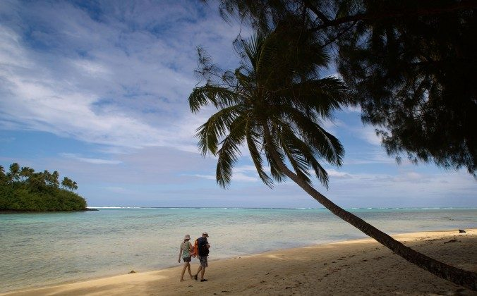 Beachgoers walk along Muri beach on the Island of Rarotonga, the largest island in the Cook Islands. A CBC program alleging lawyer Tony Merchant had a secretive bank account in the Cook Islands has prompted a libel lawsuit by merchant and his wife, Sen. Pana Merchant, against the national broadcaster. (Marty Melville/AFP/GettyImages)